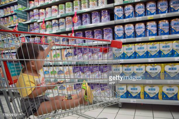 A baby stays in a shopping cart as his mother selects baby milk in a supermarket in Haikou south China's Hainan province on August 7 2013 China has...