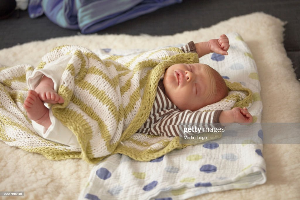 Baby Stretching On Sheepskin Rug Wrapped In Hand Knitted Green And White  Striped Blanket : Stock