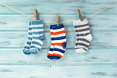 Baby striped socks on a clothesline on blue wooden background
