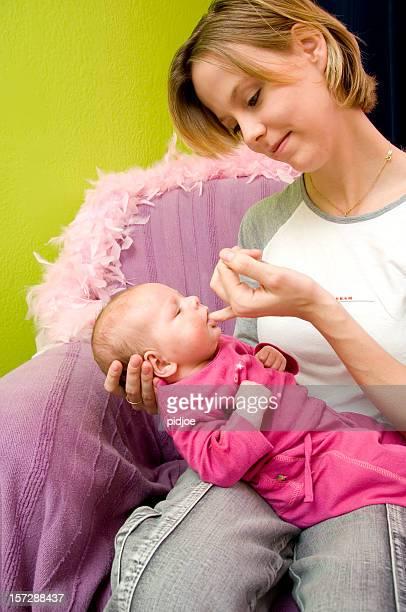 baby sucking on mother's finger