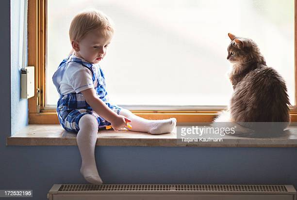 Baby / Toddler and Cat sitting on Window Sill