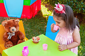Baby toddler girl playing in outdoor tea party drinking from cup with best friend Teddy Bear sitting at table. Pink dress and queen or princess crown