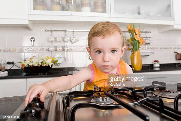 Baby touching the switches of a stove