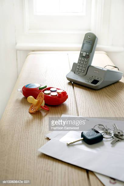 Baby toys next to telephone and keys on table, elevated view