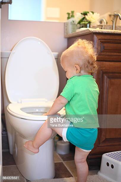 Baby trying to climb a toilet