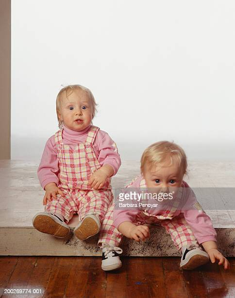 Baby twin sisters (12-18 months) sitting on step, portrait