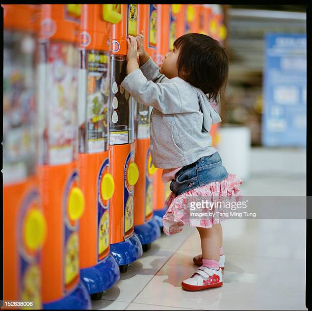 Baby waiting for toys from toy vending machine