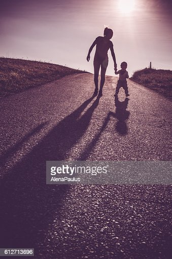 Baby walking with help of its parents - first steps