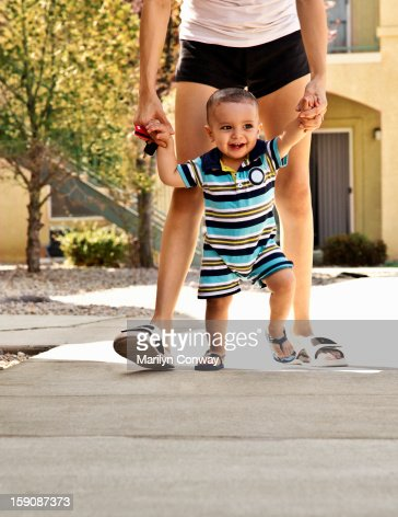 Baby walking with his mother holding his hands : Foto de stock