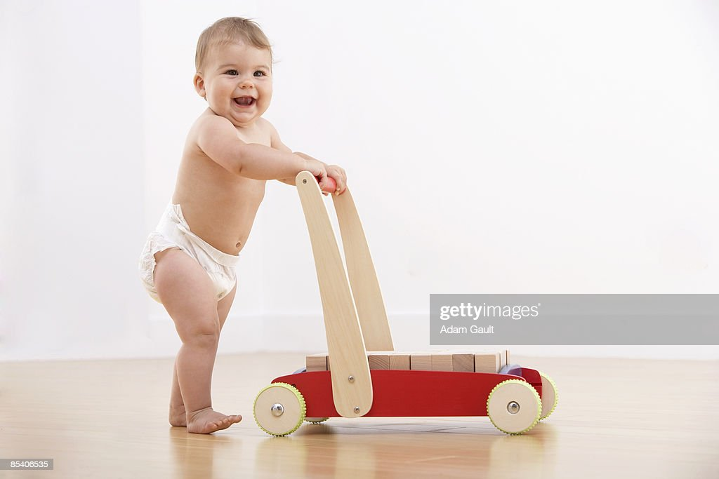 Baby walking with push cart : Stock Photo