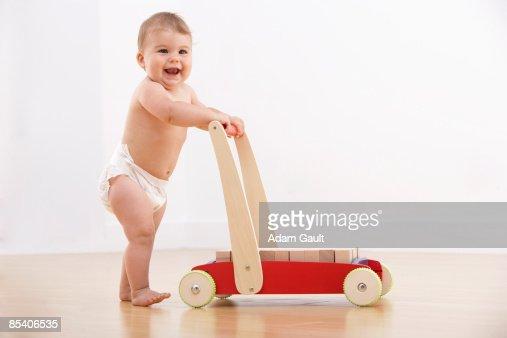 Baby walking with push cart : Foto de stock