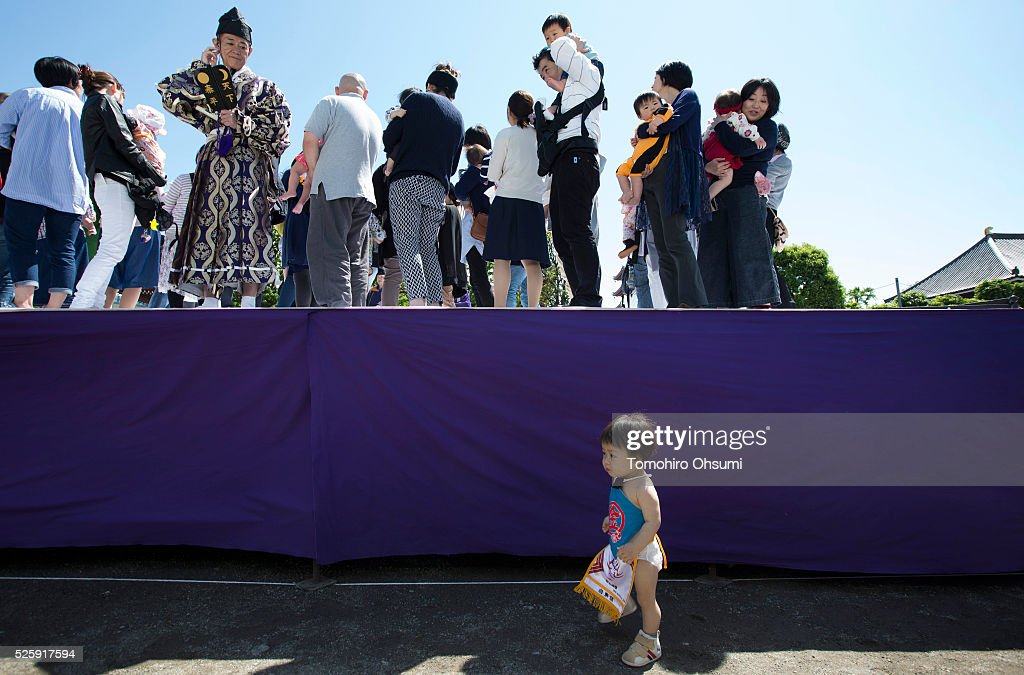 A baby walks near the stage as a referee looks on during the opening ceremony of the Nakizumo or crying baby sumo contest at Sensoji Temple on April 29, 2016 in Tokyo, Japan. Babies compete crying at this traditional festival which is believed to bring growth and good health to the infants.