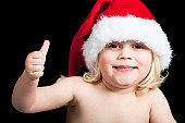 a happy christmas baby wearing a santa hat with his thumb up