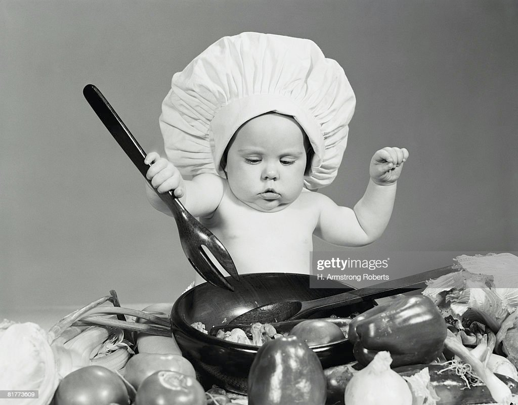 Baby wearing chef's hat, mixing salad in bowl. : Stock Photo