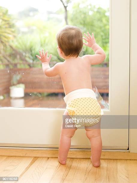 Baby wearing diaper looking out glass door