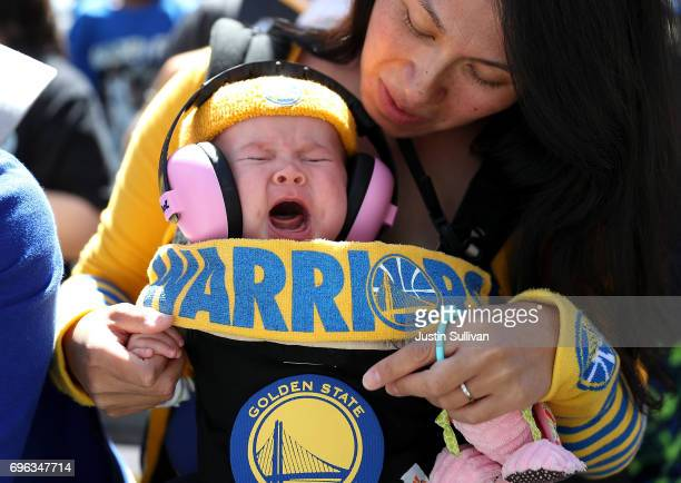 A baby wearing Golden State Warriors gear cries during the Warriors Victory Parade on June 15 2017 in Oakland California An estimated crowd of over 1...