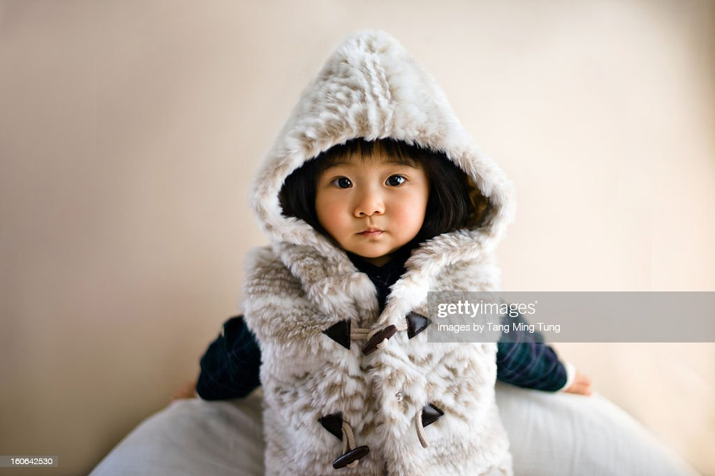 Baby wearing hoody jacket leaning on the wall : Stock Photo
