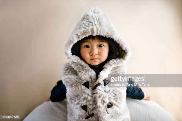 Baby wearing hoody jacket leaning on the wall