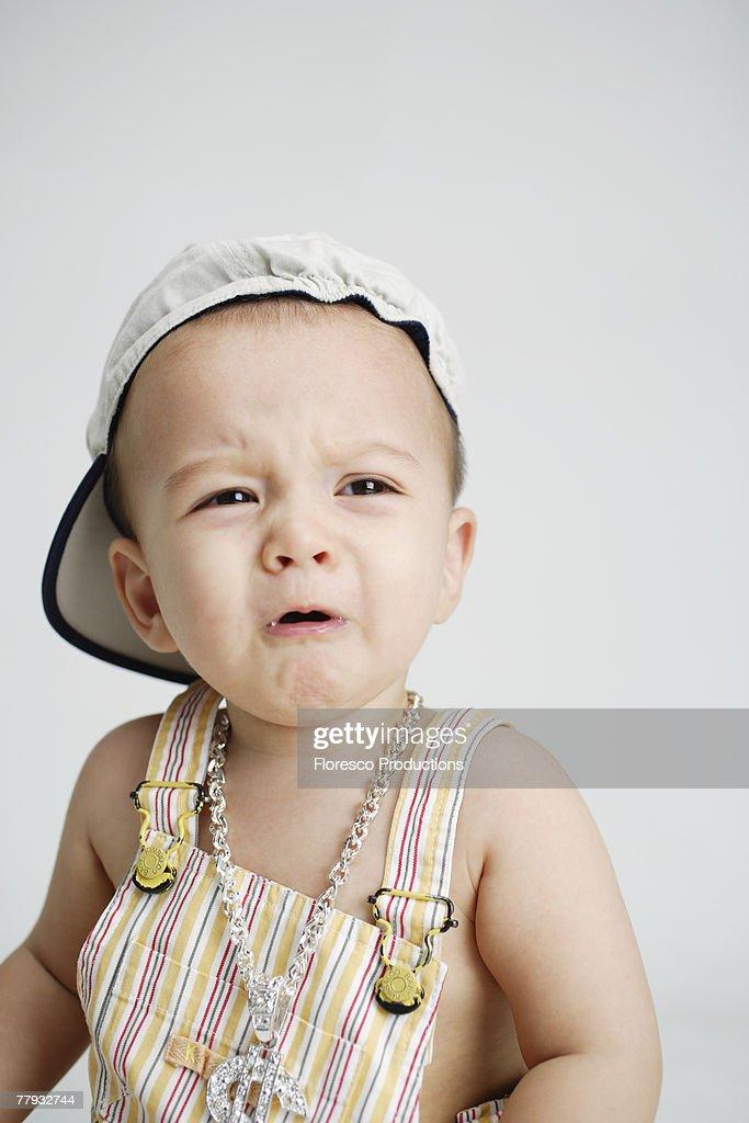 Baby wearing large money sign necklace : Stock Photo