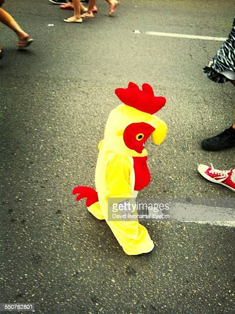 Baby Wearing Rooster Costume Walking On Street