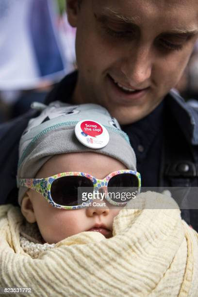 A baby wears a 'scrap the cap' badge on his hat during a nurses protest near Downing Street on July 27 2017 in London England The Royal College of...