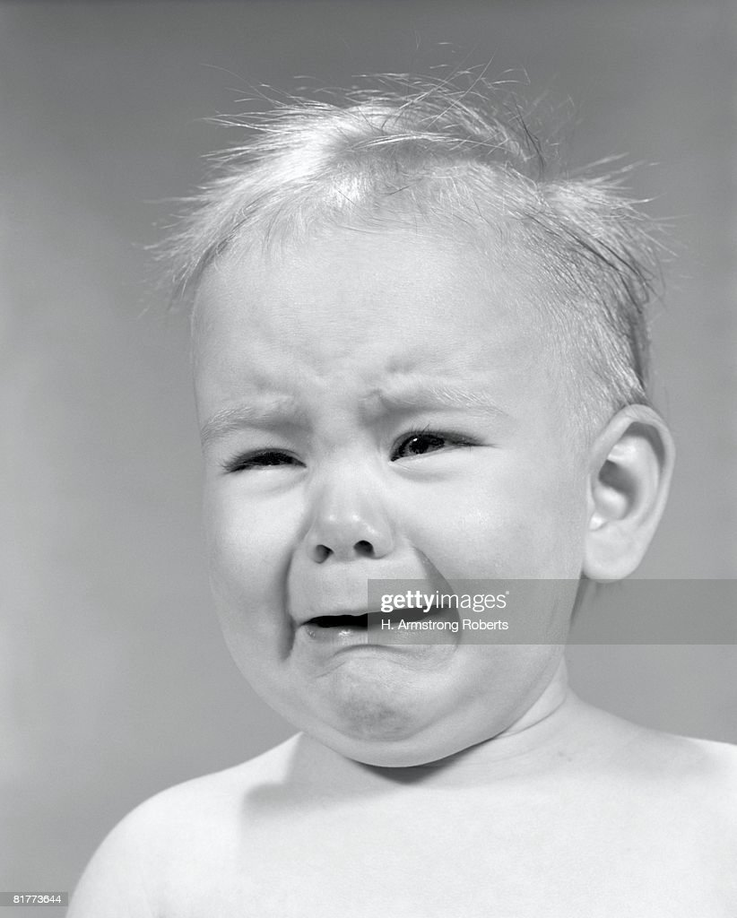 Baby wincing and crying, close-up. : Stock Photo