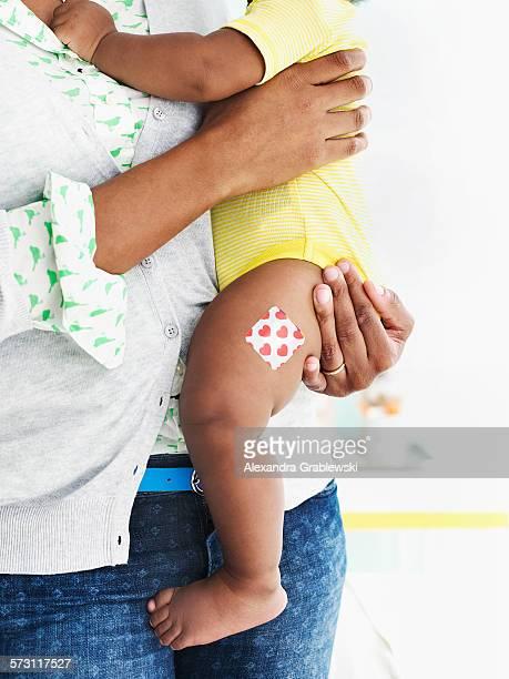 Baby with adhesive bandage on leg