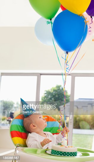 Baby with birthday cake holding balloons : Stock Photo