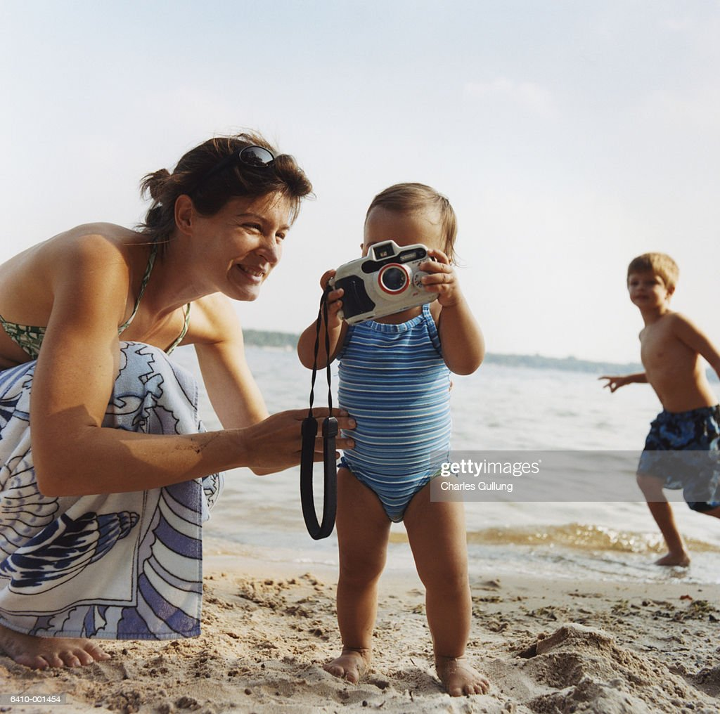 Baby with Camera on Beach : Stock Photo