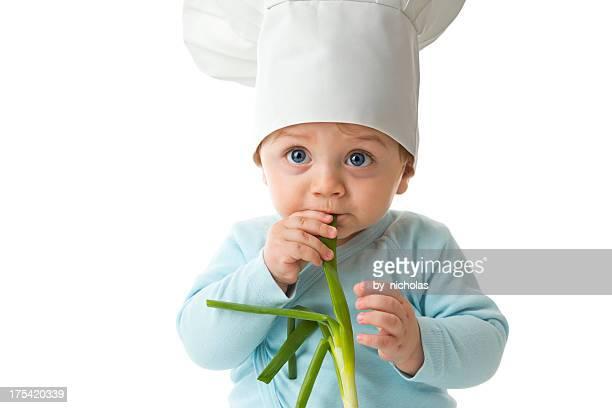 Baby mit Koch Hut und frische Zwiebel, beißen die