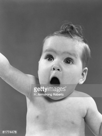 Baby with eyes and mouth wide open and surprised look on face, portrait. : Stock Photo