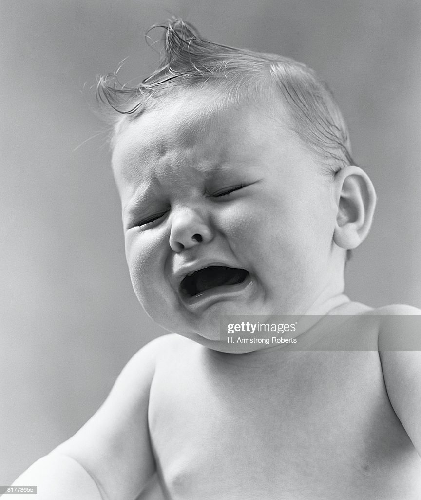 Baby with eyes closed and mouth open, frowning. : Stock Photo
