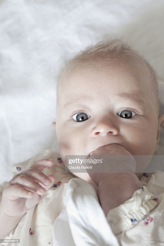 Baby with finger in his mouth : Stock Photo