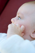 Baby with hand on face, side view