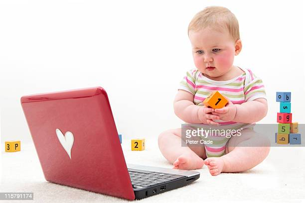 baby with learning bricks and laptop