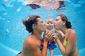 Happy swimming family - father and mother with baby swim and dive underwater with fun in swimming pool. Healthy lifestyle, active parents, water sports and swimming lessons on vacation with children.
