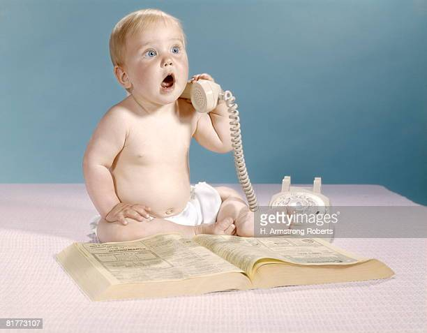 Baby With Telephone Directory Holding Telephone Receiver And Talking Studio.