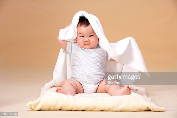 Baby (6-9 months) with towel on head and shoulders