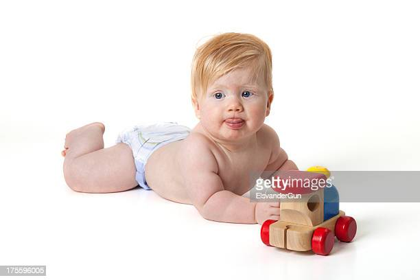 baby with wooden train