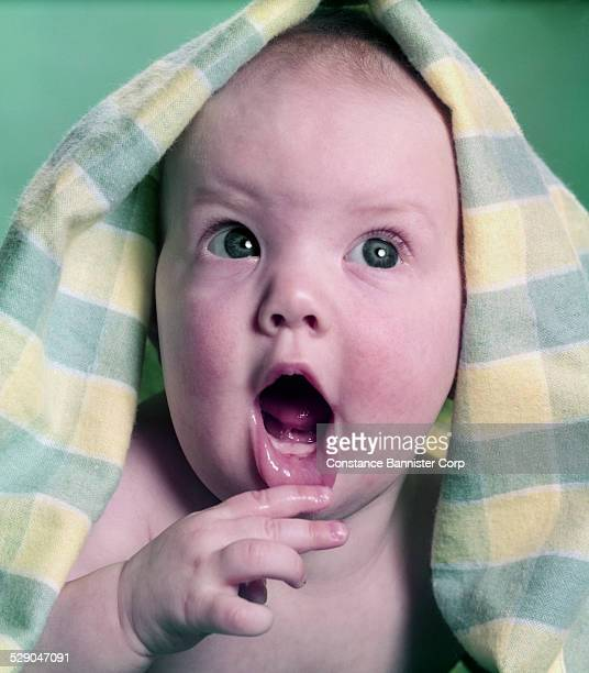 Baby with yellow and green checked blanket over head and hand holding mouth open looking up Green eyes