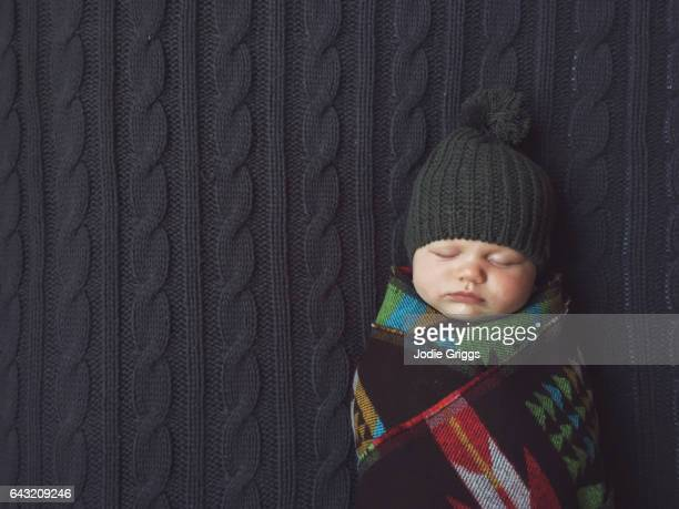 Baby wrapped up tightly laying on knitted blanket