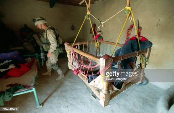 A baby's crib has been made empty as US troops search sleeping quarters of a housing compound