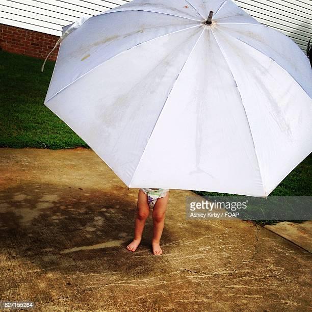 Baby's feet seen under the umbrella