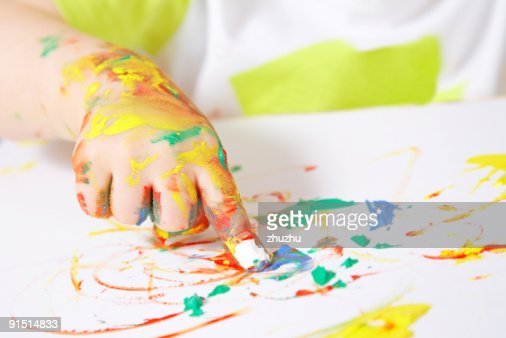 Baby's hand covered in paint while finger painting : Stock Photo