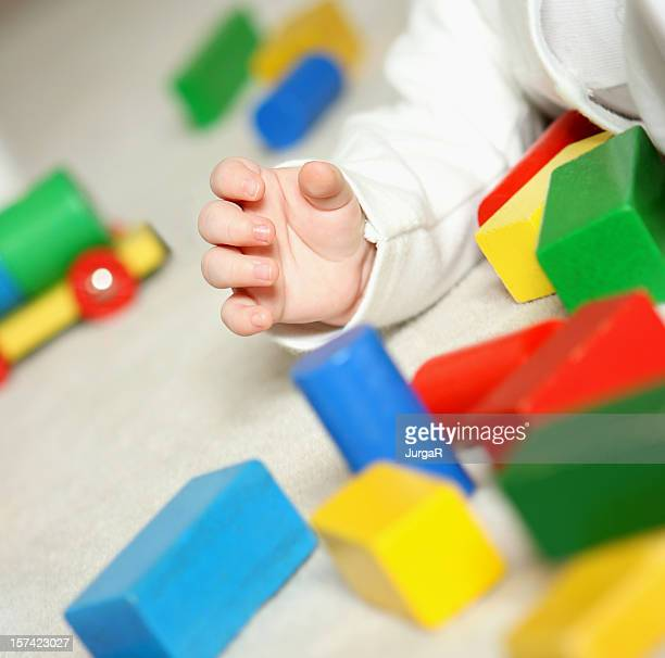 A baby's hand playing with colorful building blocks