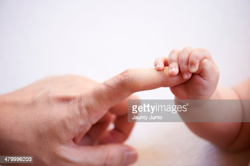 baby's small hand holding father's finger