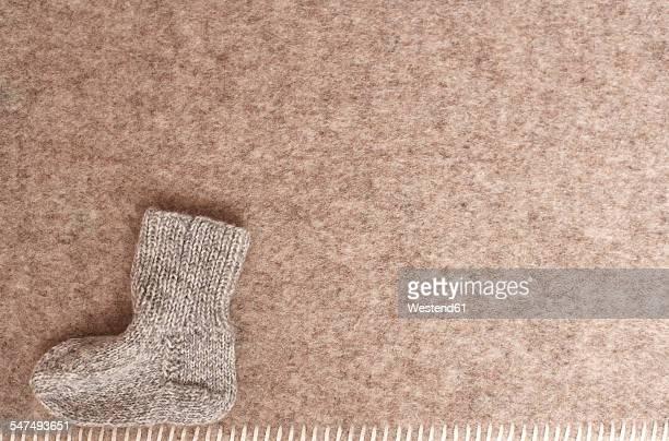 Babys woolen sock on blanket