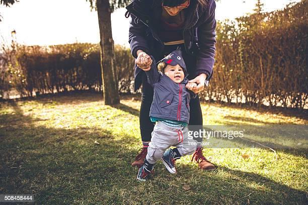 Babysitter helping baby to walk