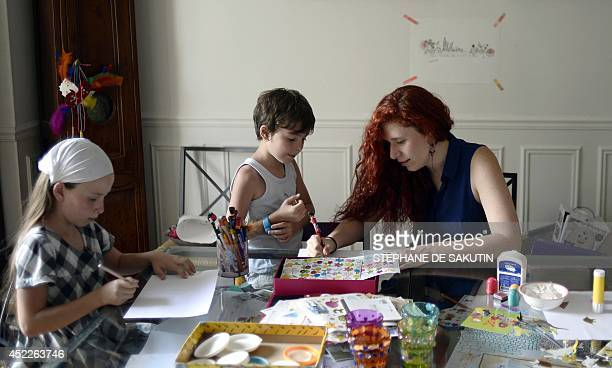 Babysitter Rosalinda makes drawings with 8yearold boy Ulysse and 10yearold girl Rose on July 16 2014 in the children's house in BourglaReine south of...
