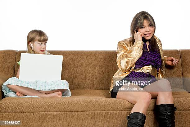 Babysitter talking on phone and girl with laptop
